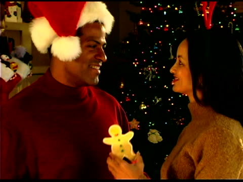 couple smiling and sharing christmas cookie - see other clips from this shoot 1407 stock videos and b-roll footage