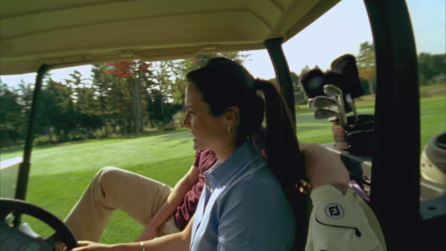 ms, couple smiling from golf cart and driving off, seco, maine, usa - golf glove stock videos and b-roll footage
