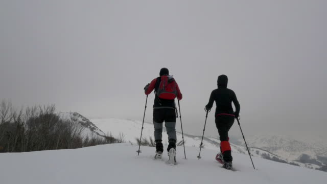 Couple snow shoeing in the top of a mountain