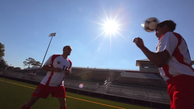a couple soccer players head a soccer ball to each other while players stretch inside a soccer stadium - head stock videos & royalty-free footage
