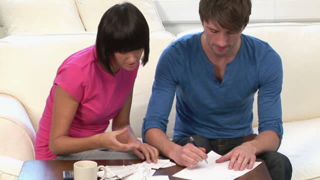 ms couple sorting receipts & using calculato on table / kinsale, ireland - stoppelbart stock-videos und b-roll-filmmaterial