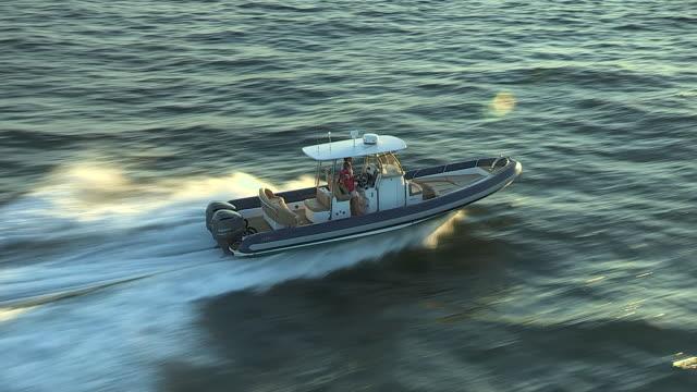 a couple speeds along narragansett bay at sunset. - vagare senza meta video stock e b–roll