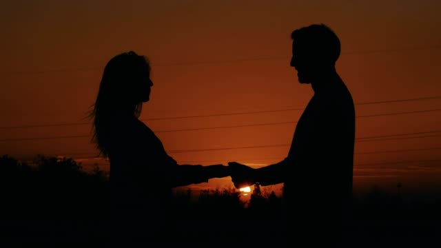 couple spinning around at sunset, silhouettes - mid adult couple stock videos & royalty-free footage