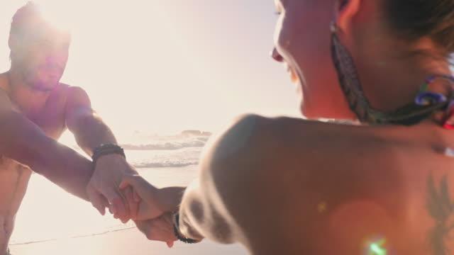 vídeos y material grabado en eventos de stock de couple spinning on beach - bañador de natación