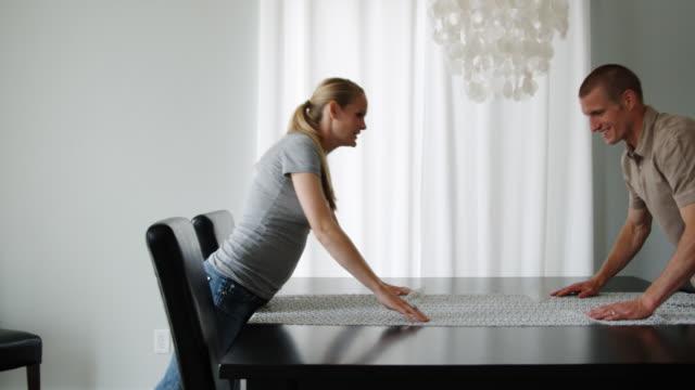 couple spreading out a tablecloth and kissing - bordsduk bildbanksvideor och videomaterial från bakom kulisserna