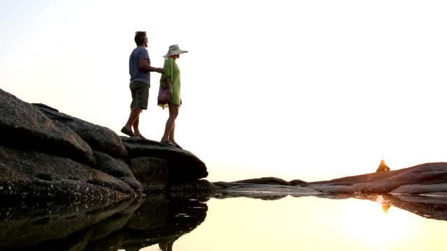 Paar stehen auf Felsen bluff über den Teich, Blick auf das Meer