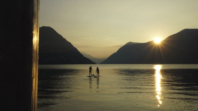 stockvideo's en b-roll-footage met couple stand up paddle board on calm lake at sunrise - peddel