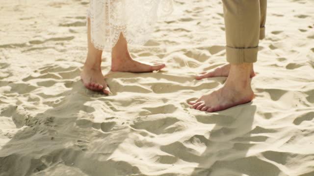 Couple Standing Strand entlang. Nahaufnahme der Füße und Wellen. Slow-Motion.
