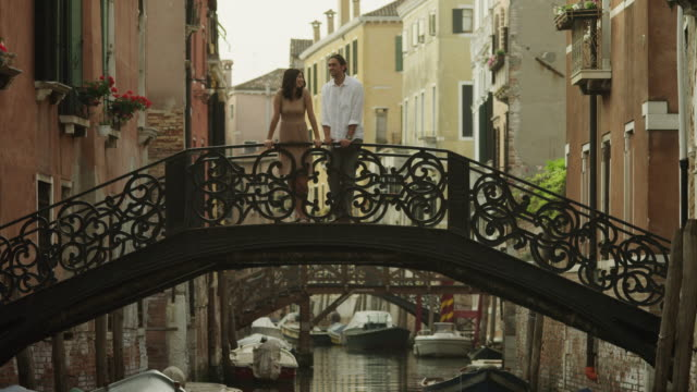 WS Couple standing and kissing on arch bridge across canal / Venice,Veneto