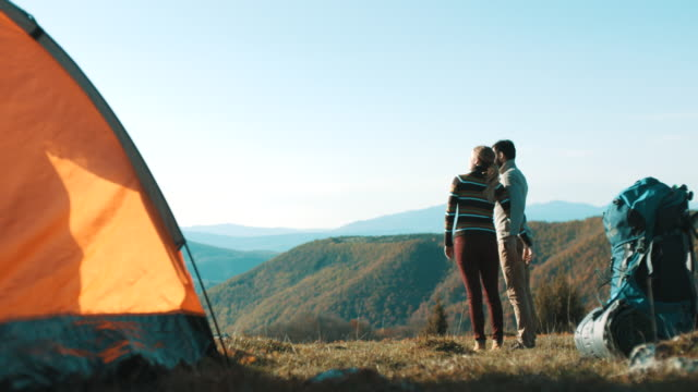 couple standing and looking in distance on mountain - distant stock videos and b-roll footage