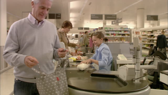 vidéos et rushes de ms couple standing at checkout and talking, cashier scanning products and passing to man / north finchley, london, uk - homme dans un groupe de femmes