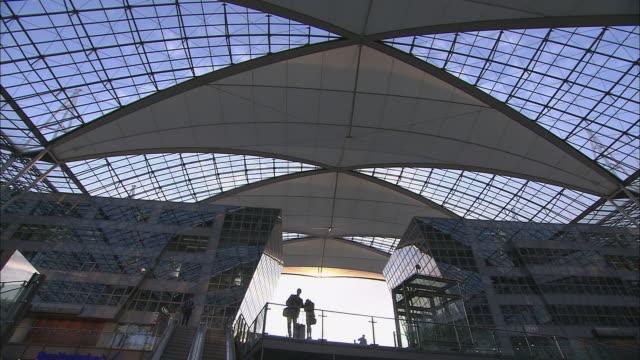 stockvideo's en b-roll-footage met la ws couple standing at railing by escalator in airport/ zi ms couple in silhouette/ munich, germany - münchen vliegveld