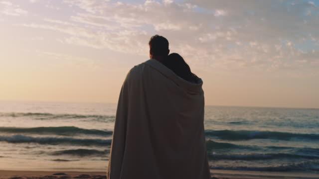 stockvideo's en b-roll-footage met paar staande op het strand - leunen