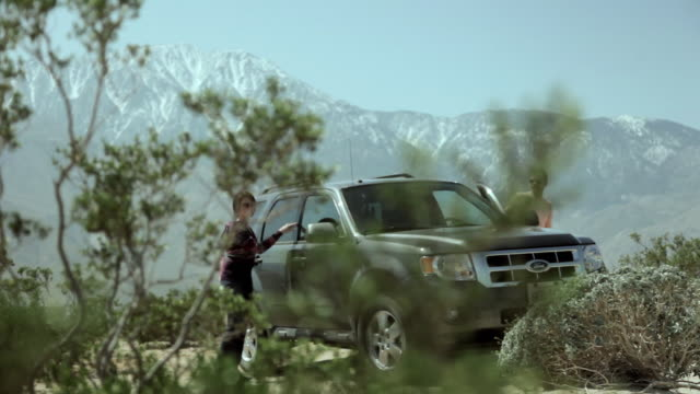 ws pan couple standing by suv embracing with mountains in background  / palm springs, california, usa - snowcapped mountain stock videos & royalty-free footage