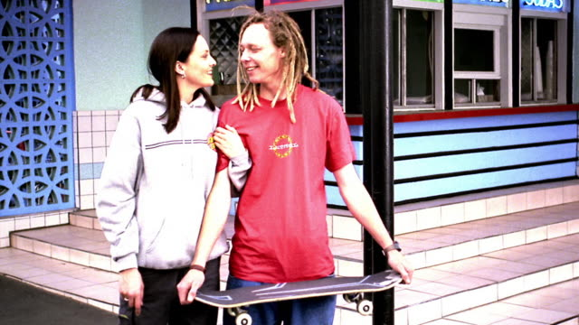 overexposed ms portrait couple standing in front of diner talking + laughing /man holding skateboard - dreadlocks stock videos & royalty-free footage