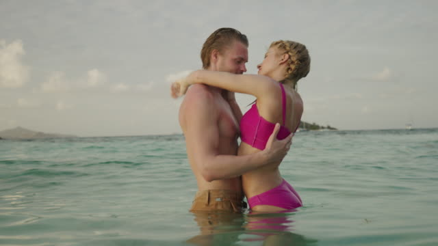 couple standing in ocean hugging and kissing / jamesby island, tobago cays, st. vincent and the grenadines - camminare nell'acqua video stock e b–roll