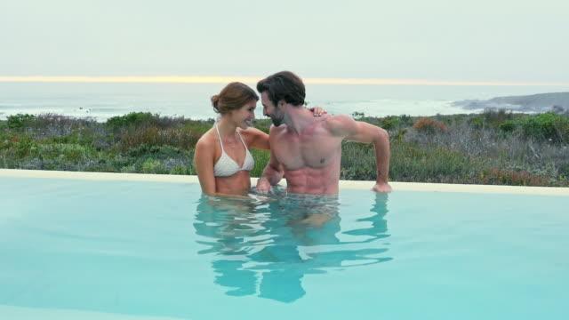 vídeos de stock, filmes e b-roll de couple standing in pool - lago infinito