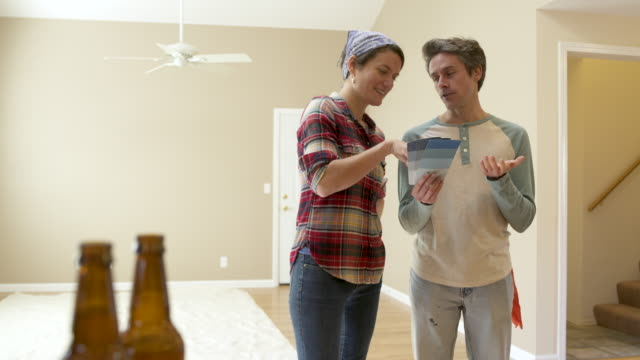 couple standing in room of new home, looking at colour swatches, panning right. - tre quarti video stock e b–roll