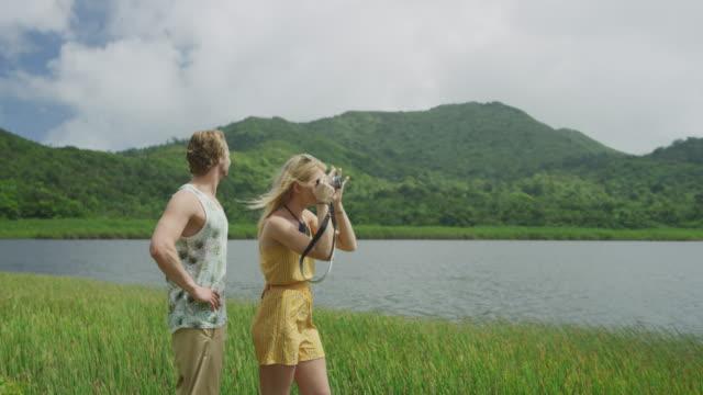 couple standing in tall grass photographing scenic view / grand etang national park, grenada - 腰に手を当てる点の映像素材/bロール