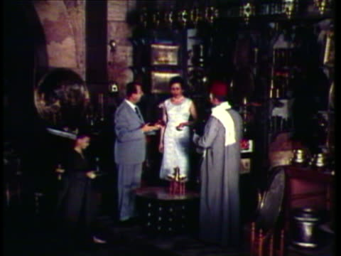 1953 WS MS Couple standing inside bazaar bartering with merchant / Morocco / AUDIO