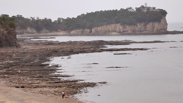 ws couple standing near sea shore at byeonsan-bando national park (the only peninsula based park in country) / buangun, jeollabukdo, south korea - south korea couple stock videos & royalty-free footage