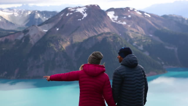 Couple standing on a mountain top looking at the beautiful view