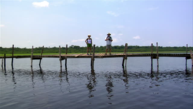 couple standing on jetty along rio negro / man looking at camera / the amazon, brazil - paar mittleren alters stock-videos und b-roll-filmmaterial