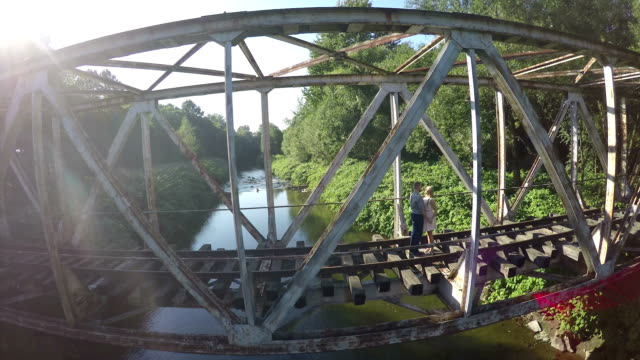AERIAL Couple standing on railroad bridge on sunny day