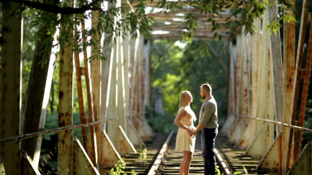 WIDE SHOT Couple standing on railroad bridge on sunny day