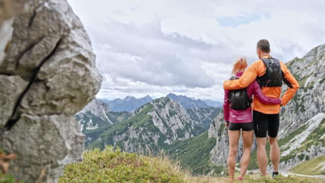 vídeos de stock, filmes e b-roll de casal de ds de pé no topo do montanha e admirar a vista sobre as montanhas circundantes - agarrar