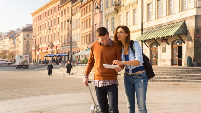 ms couple standing outdoors with trolley, using digital tablet navigation - zaino da montagna video stock e b–roll