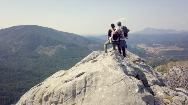 couple standing over the top of a mountain aerial view - horizont stock-videos und b-roll-filmmaterial