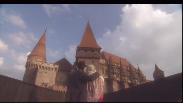 a couple stands in front of hunedoara castle. - transylvania stock videos & royalty-free footage