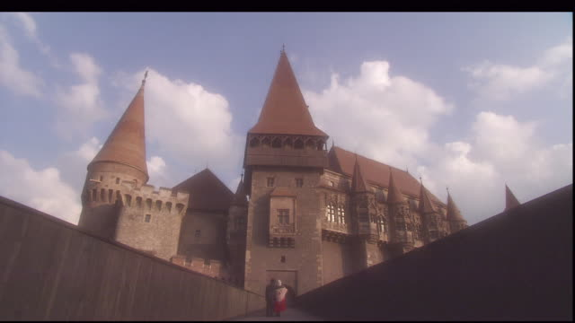 a couple stands on a walkway extending from hunedoara castle. - transylvania stock-videos und b-roll-filmmaterial