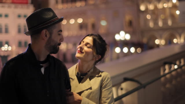 A couple stands on the balcony of a hotel and the man kisses the woman.