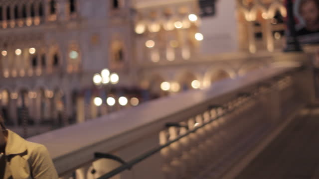 A couple stands on the balcony of a hotel at night.