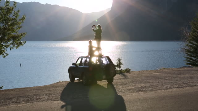 Couple stand/sit on vehicle roof, look across mountain lake