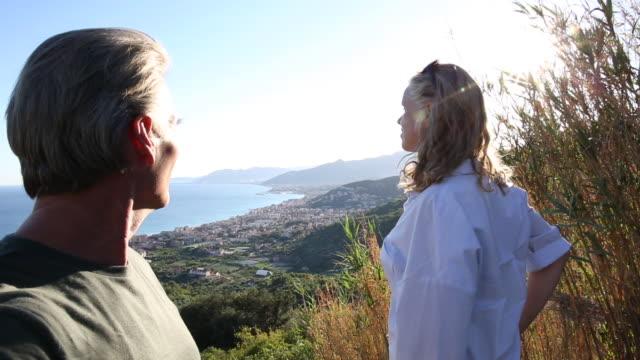 couple step onto bluff overlooking village, sea - villaggio video stock e b–roll