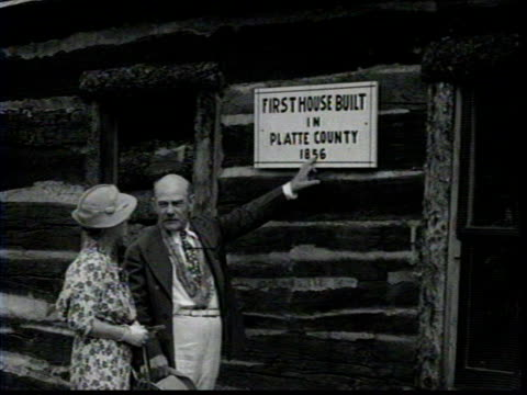 couple steps out of an historical log cabin / older couple points to sign on cabin that reads first hourse built in platte county 1856 / close up of... - 1931年点の映像素材/bロール