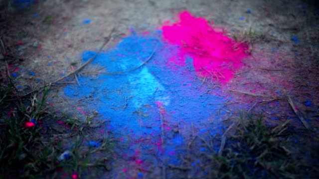 Couple stomping foot on colored powder on the ground