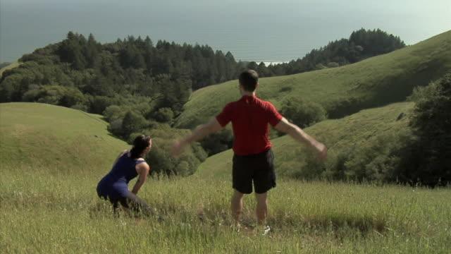 MS PAN HA Couple stretching before jogging on hill overlooking sea, Mount Tamalpais, California, USA