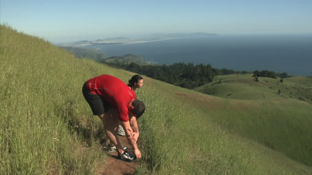 MS Couple stretching before jogging on hill overlooking sea, Mount Tamalpais, California, USA