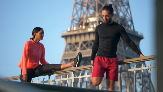 vidéos et rushes de a couple stretching before running across a bridge with the eiffel tower. - slow motion - barbe