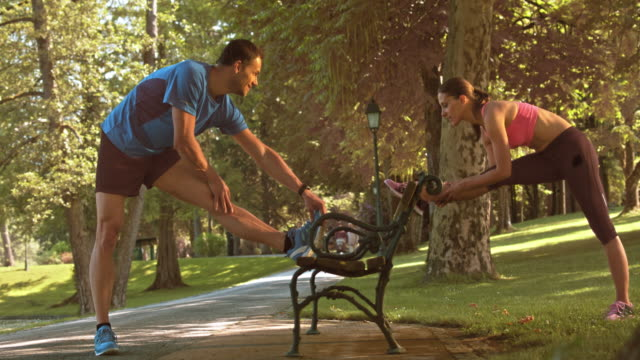 slo mo ds couple stretching on a park bench - 30 39 years stock videos & royalty-free footage