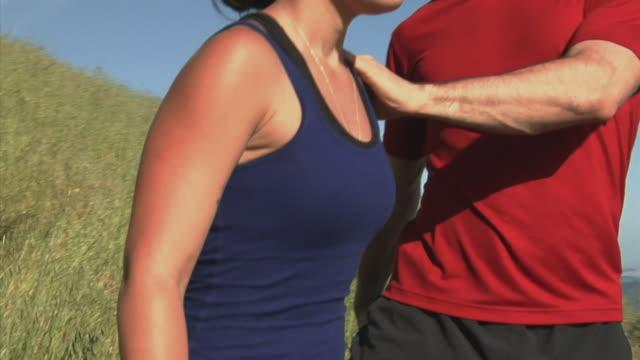 CU ZI, TD TU PAN Couple stretching standing on hill then jogging away, Mount Tamalpais, California, USA