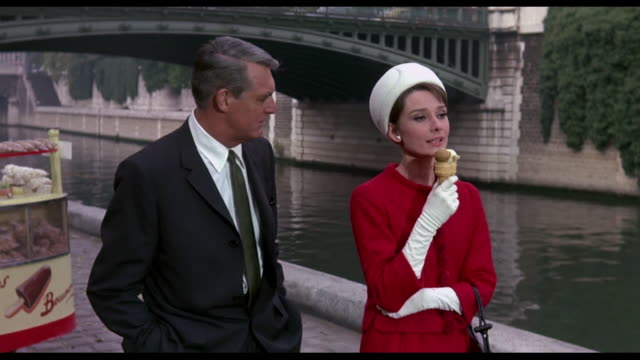 1963 couple (cary grant and audrey hepburn) stroll along the river seine eating ice-cream - audrey hepburn stock videos & royalty-free footage
