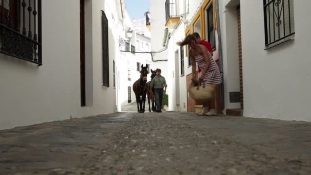 couple strolling through quaint village stand aside to let man with donkey pass and take photos with camera and mobile phone/genalguacil/andalucia/spain - the spanish donkey stock videos & royalty-free footage
