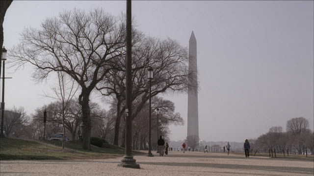 ws a couple strolling through the national mall with the washington monument in the background / washington d.c., united states - washington monument washington dc stock videos & royalty-free footage