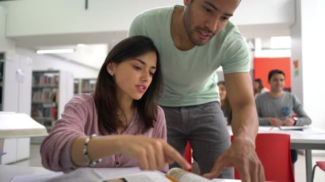 vídeos de stock, filmes e b-roll de casal da biblioteca lendo livros e homem apontando algo enquanto ambos estão falando - university student