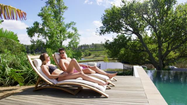 vídeos y material grabado en eventos de stock de couple sunbathing - tumbona